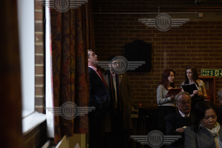 UKIP leader Nigel Farage, with his head of strategy Raheem Kassam, rests his head against the wall of the Cliffsend Village Hall, near Ramsgate in Kent during campaigning for the 7 May 2015 general election.