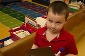 MR / Schenectady, NY. Zoller Elementary School (urban public school). Kindergarten inclusion classroom. Portrait of student (boy, 5) with clipboard at learning center time. MR: Gia3. ID: AM-gKw. © Ellen B. Senisi.
