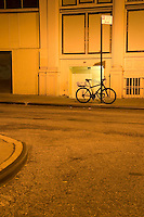 AVAILABLE FROM JEFF AS A FINE ART PRINT.<br /> <br /> AVAILABLE FROM JEFF FOR COMMERCIAL AND EDITORIAL LICENSING.<br /> <br /> Bicycle Chained to Street Sign Post at Night, Lower Manhattan, New York City, New York State, USA