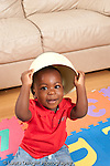 12 month old baby boy sitting on floor with bowl in his head peek a boo vertical portrait
