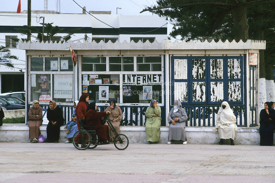 Essaouira, Morocco - Women Sitting in Town Square, Place Moulay El-Hassan.  Internet Cafe, Cyber Cafe, Wheel Chair, Traditional Dress