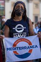 """NGO: Mediterranea.<br /> <br /> Rome, 27/07/2020. Today, hundreds of people, NGO's (ONG) representatives, actors and politicians gathered in Piazza San Silvestro (near the Italian Parliament) to protest (1.) against the dramatic situation in Libya - erupted in a civil war between the GNA (2.) and the forces of General Khalifa Belqasim Haftar - and to protest against the inhumane conditions of migrant people trapped in legal and illegal prisons in Libya. The aim of the demo was to call the Italian Government to stop funding the """"Libyan Coast Guard"""" and to immediately help and free People in Libya throughout """"Humanitarian Corridors"""", and give them the protection they are entitled of by the International Human Rights Conventions. <br /> From the organisers Facebook event page: «[…] we meet to ask the Italian Government and the European States to stop funding the so-called Libyan coast guard, to close and evacuate the detention centres by transferring migrants out of Libya and to promote corridors to help people on the run find protection without endangering their lives. The men, women and children who take the sea from the Libyan coast flee from situations of extreme misery, despotic regimes, tribal persecutions, ethnic conflicts, wars and environmental catastrophes. And in Libya they are subjected to violence, extortion, detention, torture, rape and torture. A few days ago, on July 16, the Chamber of Deputies [Of the Italian Parliament, ndr] for the fourth consecutive year approved the financing of the Italian mission in Libya, which provides financial support for the so-called Libyan coastguard and training and training of its members. […] The mobilization will be accompanied by readings by Ascanio Celestini, Valentina Carnelutti, Fabrizio Gifuni and Sonia Bergamasco […]».<br /> <br /> Footnotes & Links:<br /> 1. https://www.facebook.com/events/2732849460337428/<br /> 2. 07.05.19 Prime Minister of Libya Fayez al-Serraj Met Italian PM Giuseppe Conte at Palazzo Chigi h"""