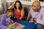Family at home seven year old girl with father and step-mother playing strategy board game Blokus using colored tiles