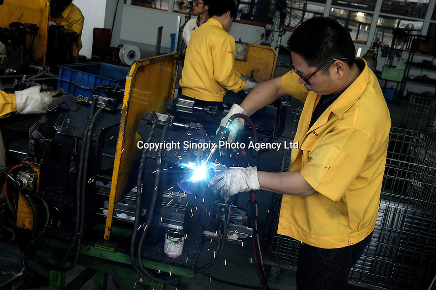 Welding on production line in a privately owned metal works factory, producing parts for major foreign companies including Fuji Xerox, Panasonic, Black & Decker and DeWalt, both for Chinese market and for export (including UK, US and Japan).