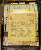 A set of instructions sits on letterpress matrices in the workshop of the Dale Guild Foundry.