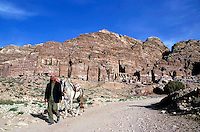 Man walking with his horse near the entrance to the Royal Tombs carved into the cliffs at Petra, Jordan.