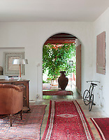 A spacious passage leads from the living room, past an antique desk and chair, out to the flower room