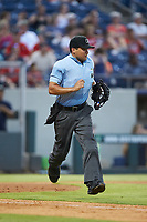 Home plate umpire Charlie Ramos hustles down the first base line during the International League game between the Scranton/Wilkes-Barre RailRiders and the Gwinnett Stripers at Coolray Field on August 16, 2019 in Lawrenceville, Georgia. The Stripers defeated the RailRiders 5-2. (Brian Westerholt/Four Seam Images)