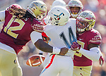 Florida State defensive tackles Demarcus Christmas, right, and Arthur Williams strip the ball from Delaware State running back Nyfease West in an NCAA football game in Tallahassee, Fl.  Florida State defeated Delaware State 77-6.