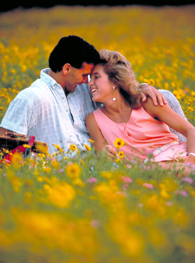 Young lovers in field of wild flowers. man, woman, couples, romance, love. Tanya Giauque, Dan Trueluck.
