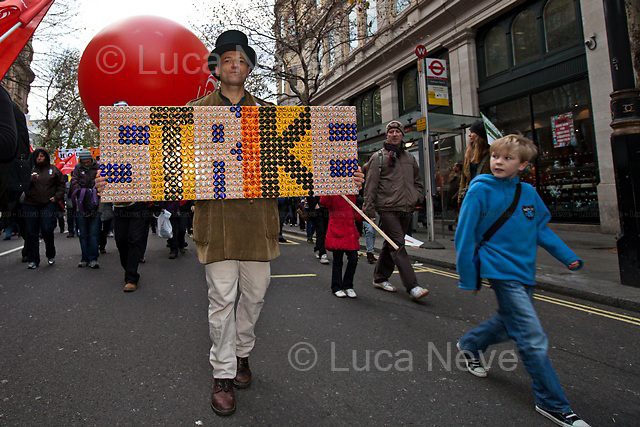 Protester - 2011<br /> <br /> London, 30/11/2011. An estimated 2.6 million public sector workers went on strike today in the UK against pension reform and cuts to public services that the Coalition Government is pushing through Parliament. A march in central London saw tens of thousands protesting against the Governments new policies and austerity measures. Heavy police presence was met with indignation especially in Trafalgar Square, which was literally divided in two using the steel riot walls (metal cordons) built to prohbit the protesters reaching Whitehall. At around 15:00, dozens of protesters stormed the office of the mining company XStrata in Panton Street (near Piccadilly Circus and Leicester Square) but they were quickly evicted by police officers. 20 arrests were made. There were some clashes between police officers and protesters when the police coach carrying those arrested attempted to leave Haymarket.