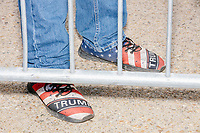 A man wears Trump-themed shoes near a crowd-control barrier before the arrival of US President Donald Trump at a Make America Great Again Victory Rally in the final week before the Nov. 3 election at Pro Star Aviation in Londonderry, New Hampshire, on Sun., Oct. 25, 2020.