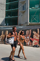 Sunny Beach, Nesebar, Bulgaria..Holidaymakers walk past advertising for a strip club in front of a construction site at Sunny Beach, the largest holiday resort in the Balkans, and a popular destination for cheap foreign package tours. Rapid overdevelopment of the Back Sea coast has led to widespread environmental destruction, and many properties lie uncompleted or empty.