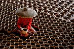 Workers arrange pottery by Gatot Herliyanto