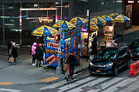NEW YORK, NEW YORK - FEBRUARY 4:  People buy food in a street cart in Times Square on February 12, 2021 in New York. New York City is getting back their indoor dining with a restriction of 25 percent capacity. most of the restaurants have set up outdoor dining structures like pods, bubbles and lot of makeshift cabins. (Photo by Eduardo MunozAlvarez/VIEWpress)