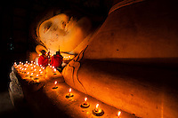 Two monks worshipping at the 18m long reclining Buddha in Bagan, Myanmar