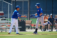 Toronto Blue Jays coach Luis Hurtado congratulates Griffin Conine (17) after hitting a home run during a Minor League Spring Training game against the Detroit Tigers on March 22, 2019 at the TigerTown Complex in Lakeland, Florida.  (Mike Janes/Four Seam Images)
