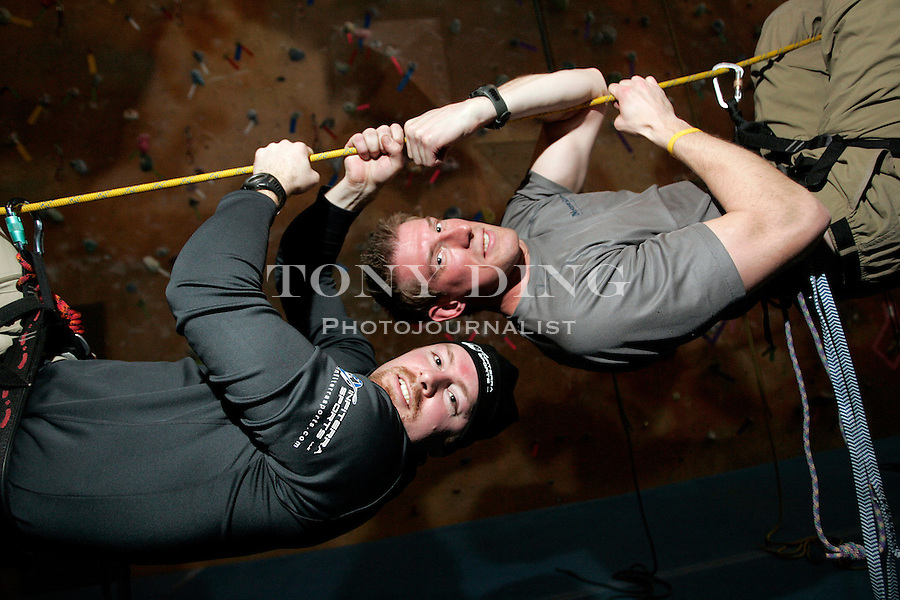 Chad Lambert, top, and Zac Chisholm of Infiterra Sports hang upside-down from a rope at Planet Rock Climbing, on Saturday, March 25, 2006, in Ann Arbor, Mich. Lambert and Chisholm, both 29, are partners in an outdoor adventures company that set up races of running, biking, boating, orientering.