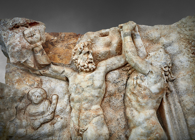 Close up of a Roman Sebasteion relief sculpture of Zeus and Prometheus, Aphrodisias Museum, Aphrodisias, Turkey.  Against a grey background. <br /> <br /> Prometheus is screaming in pain. Zeus had given him a terrible punishment for giving fire to man: he was tied to the Caucasus mountains and had his liver picked out daily by an eagle. Herakles shot the eagle and is undoing the first manacle. He wears his trade mark lion-skin and thrown his club to one side. A small mountain nymph, holding a throwing stick appears amongst the rocks.