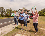 May 5, 2018. Fayetteville, North Carolina.<br /> <br /> (left to right) Katie Gallagher, Debra Grabauskas, unknown and Vanessa Hall hold signs about the GenX pollution of the Cape Fear River on Hwy. 87 just outside the Chemours plant which has been dumping GenX unregulated into the river for years. <br /> <br /> The Chemours Company, a spin off from DuPont, manufactures many chemicals at its plant in Fayetteville, NC. One of these, commonly referred to as GenX, is part of the process of teflon manufacturing. Chemours has been accused of dumping large quantities of GenX into the Cape Fear River and polluting the water supply of city's down river and allowing GenX to leak into local aquifers.