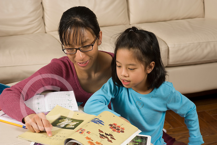 8 year old girl at home doing homework for Chinese language class,helped by mother horizontal