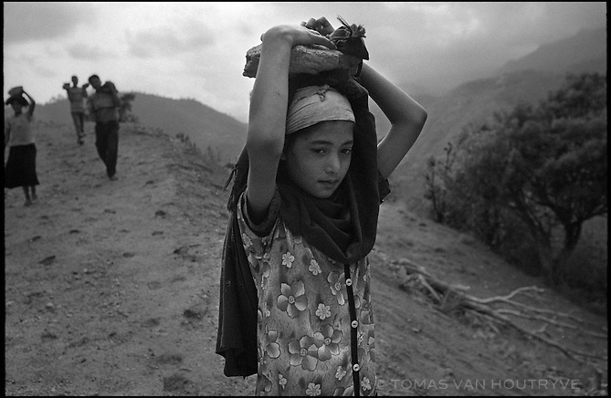 A civilian girl carries rocks on her head during construction of the Maoist rebel's Martyrs' road near the village of Nuwagaun in the Maoist controlled district of Rolpa on 23 June 2005. The Maoists required one person from each household in Rolpa and Rukum districts to contribute to the construction of the road for 10-15 days. The road built completely by hand labor is the first one to connect to the rural villagers in this area.<br />