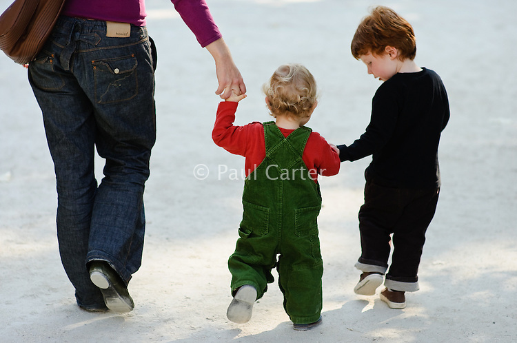 Mother and two sons walking along holding hands.