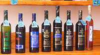 Wine bottles on a shelf for sale in the winery shop: Posip, Viva, Plavac, Potomje, Postup, Dingac and Prosek. With price tags around the necks. Matusko Winery. Potmje village, Dingac wine region, Peljesac peninsula. Matusko Winery. Dingac village and region. Peljesac peninsula. Dalmatian Coast, Croatia, Europe.