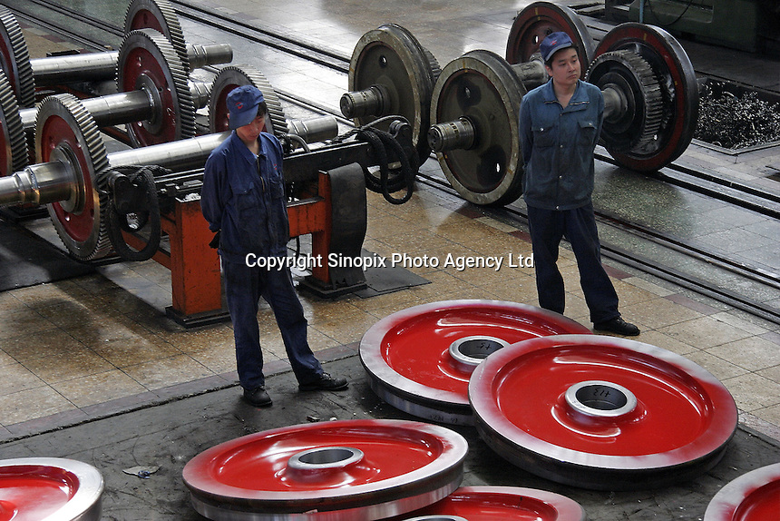 Chinese workers stand near a group of locomotive wheels at the state-owned Datong Electric Locomotive Co. LTD in Datong, Shanxi Province, China. China's developing economy has created a huge demand for faster and more powerful locomotive engines to move its people and goods within its vast and expanding railway network, the Datong company is currently working together with several western partners including Alstom of France and ABC of the U.S..05 Jul 2005