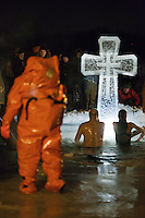 Moscow, Russia, 19/01/2011..An emergency worker watches as Orthodox Christian believers celebrate Epiphany at a lake in eastern Moscow. Priests blessed the waters and followers baptised themselves by total immersion in the freezing lake in temperatures of minus 15C.