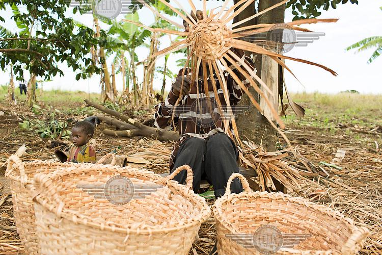 Matayo Sengoma (45) waving baskets from banana leaves.