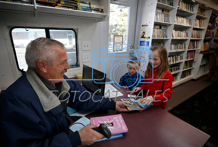 Elko County Bookmobile driver Kelvin Selders checks out books for Quincy and Natalie Dahl, 5 and 8, during a visit to the Ruby Valley School.<br />Photo by Cathleen Allison/Nevada Momentum