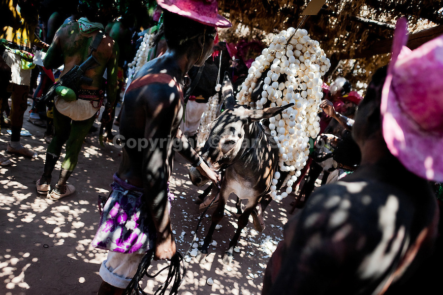 """A Cora Indian boy, covered with hundreds of eggshells, sits on a donkey during the sacred ritual celebration of Semana Santa (Holy Week) in Jesús María, Nayarit, Mexico, 22 April 2011. The annual week-long Easter festivity (called """"La Judea""""), performed in the rugged mountain country of Sierra del Nayar, merges indigenous tradition (agricultural cycle and the regeneration of life worshipping) and animistic beliefs with the Christian dogma. Each year in the spring, the Cora villages are taken over by hundreds of wildly running men. Painted all over their semi-naked bodies, fighting ritual battles with wooden swords and dancing crazily, they perform demons (the evil) that metaphorically chase Jesus Christ, kill him, but finally fail due to his resurrection. La Judea, the Holy Week sacred spectacle, represents the most truthful expression of the Coras' culture, religiosity and identity."""