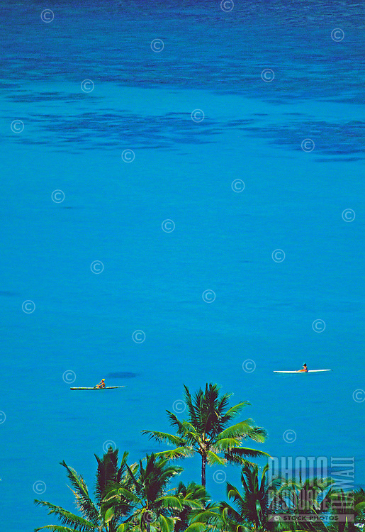 Two kayaks glide peacefully on the calm blue ocean off Lanikai on the windward side of Oahu. Shot through a foreground of coconut palm tops.