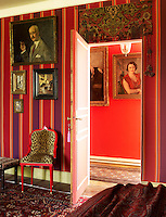 The exotic interior of one of the guest bedrooms which features a red and purple striped wall fabric and cashmere bed covers