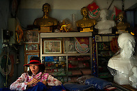A shopkeeper is surrounded by busts and images of Ho Chi Minh inside a store in Hue, Vietnam on 26 February 2010.