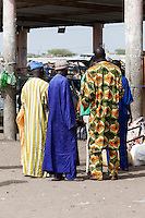 Senegal, Saint Louis.  Men in Colorful African Boubous, at Bus and Taxi Station.