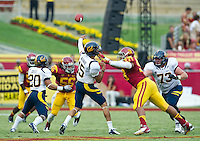 LOS ANGELES, CA - September 22, 2012:  USC linebacker Marquis Simmons (53) applies pressure to Cal Bears quarterback Zach Maynard (15) during the USC Trojans vs the Cal Bears at the Los Angeles Memorial Coliseum in Los Angeles, CA. Final score USC 27, Cal 9..