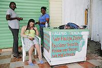 Dominican Republic. La Altagracia Province. Coastal resort of Punta Cana. Playa Bavaro. El Cortecito. Two black women are making braids for a young white english tourist woman. © 2006 Didier Ruef