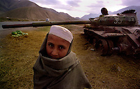 Salang Pass / Afghanistan.Un giovane afgano lungo la strada strategica del Passo del Salang che collega Kabul al nord dell'Afghanistan. Sullo sfondo i resti di un carro armato distrutto.<br /> Foto Livio Senigalliesi.<br /> Salang Pass / Afghanistan.Young boy selling fruits along the road of Salang Pass connecting Kabul with the north of Afghanistan.On the background one tank destroyed during the war.<br /> Photo Livio Senigalliesi