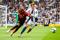 Ashley Young of Manchester United (18) Solly March of Brighton & Hove Albion (20)  challenge for the ball  during the Premier League match between Brighton and Hove Albion and Manchester United at the American Express Community Stadium, Brighton and Hove, England on 19 August 2018. Photo by Edward Thomas / PRiME Media Images.