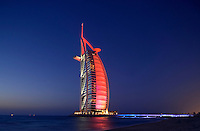 Burj al Arab Hotel, architects W. S. Atkins,  an icon of Dubai built in the shape of the sail of a dhow, stands on an artificial island just off Jumeirah Beach. Evening.  Dubai. United Arab Emirates.