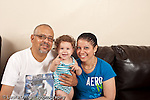 13 month old baby girl at home portrait on couch with parents horizontal