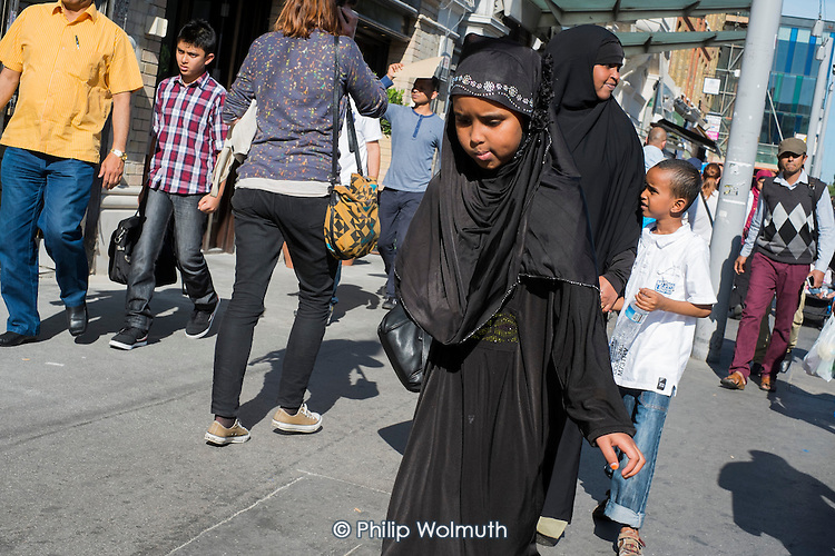 Pedestrians in Whitechapel High Street.  The area is home to the largest Muslim community in the UK.