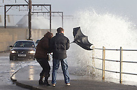 A couple walk along the shore line near Saltcoats as a major winter storm moves in over Scotland..The Met Office has issued its highest warning, a red alert..Hundreds of schools have been shut and bridge and road closures are causing disruption. 90mph winds are expected..Parts of England and Northern Ireland are also being hit by extreme wind and rain..Picture: Universal News And Sport (Scotland). 8 December 2011. www.unpixs.com.