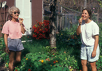 Women picking & eating edible flowers nasturtium in garden