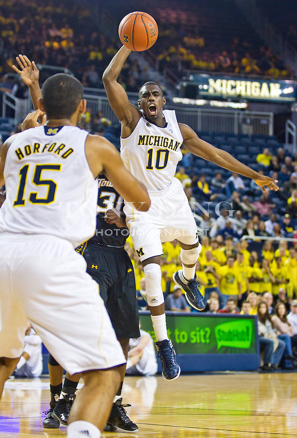 Michigan guard Tim Hardaway, Jr. (10) jumps to pass the ball to Jon Horford (15) in the second half of an NCAA college basketball game against Towson, Monday, Nov. 14, 2011, at Crisler Arena in Ann Arbor. Michigan won 64-47. (AP Photo/Tony Ding)