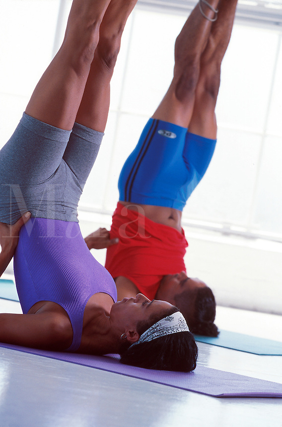 Man and woman practicing yoga shoulder stands together.