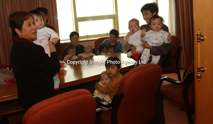 "Nannies and minders arrive at a five-star hotel in China to hand over babies for adoption.  The ""hand-over"" is an emotionally charged event with babies, parents and nannies in tears."