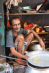 Life is lived outdoors for many in Kolkata, here a man sells cheap rice and curry meals from his tiny streetside stall.